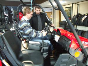 Jason Lannon, left, owner of M&F Motors in Stephenville, Nfld., shows potential buyer Bill Oliver the features on the Yamaha Rhino.