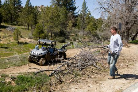 "Steve Nessl, Yamaha's Marketing Manager participates in a project to help prevent unauthorized trails from developing.  Called ""slashing"", this entails using downed trees and brush to block off any newly developing trails appearing in the surrounding area."