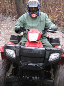 ATV guide and test rider Les Pinz pushes the Polaris hard through a mud pool.