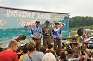 Corbin Knox, Brian Wolf, and Josh Kirkland celebrate on the XC2 podium.