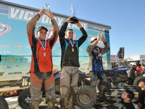 Gabe Phillips, Walker Fowler, and Parker Jones celebrate on the XC2 podium.